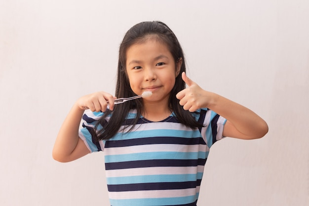 Piccoli denti svegli asiatici della spazzola della ragazza