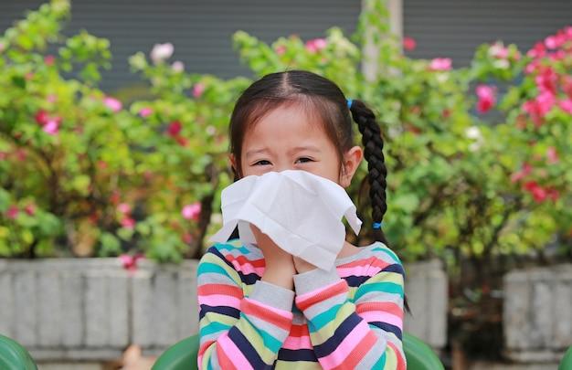 Piccola ragazza asiatica che soffia il naso con seduta di carta velina all'aperto.
