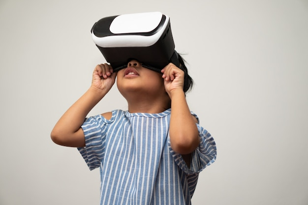 La piccola bambina asiatica con l'auricolare per realtà virtuale è eccitante per una nuova esperienza. Foto Premium