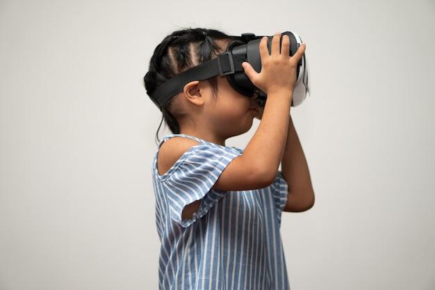 La piccola bambina asiatica con l'auricolare per realtà virtuale è eccitante per una nuova esperienza.