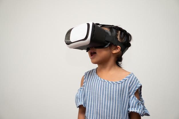 Piccolo bambino asiatico della ragazza con la cuffia avricolare di realtà virtuale