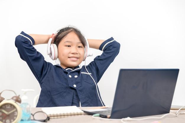 Piccola ragazza asiatica che fa i compiti sul computer portatile