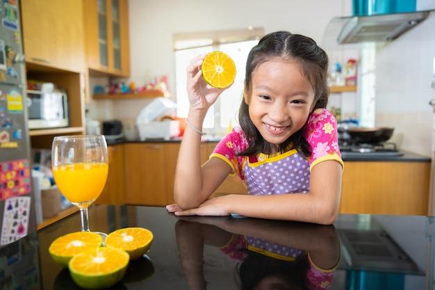 Piccola ragazza asiatica che beve il succo di arancia in cucina