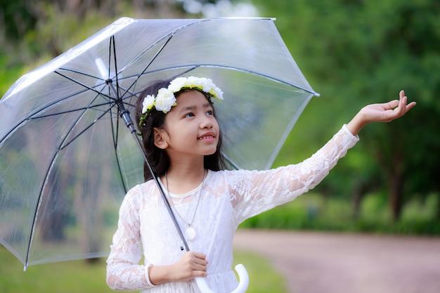 Piccola ragazza asiatica che tiene chiaro ombrello e che sorride con la felicità