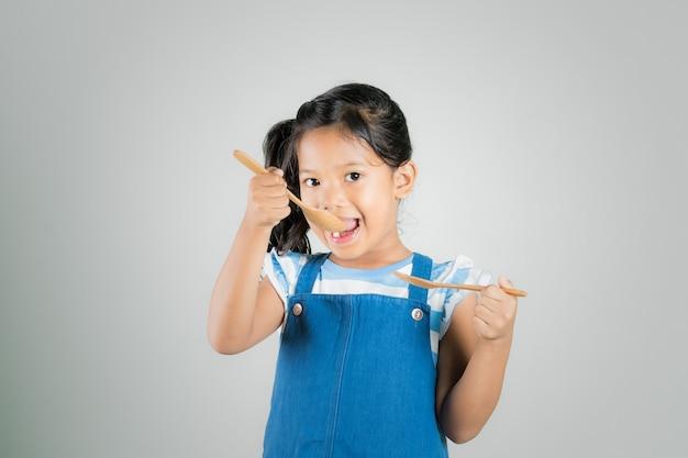 Piccola ragazza asiatica che tiene cucchiaio e forchetta, ragazza affamata, concetti di stile di vita dieta.