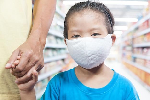Piccoli bambini asiatici della ragazza che indossano mascherina protettiva medica