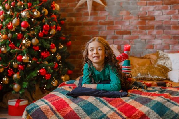 Piccola ragazza asiatica in pigiama nella camera da letto sdraiata sul letto vicino all'albero di natale natale capodanno