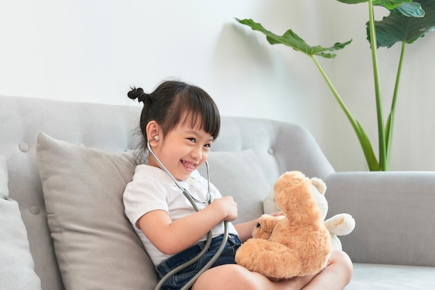 La piccola ragazza asiatica gioca con il giocattolo della bambola del bambino