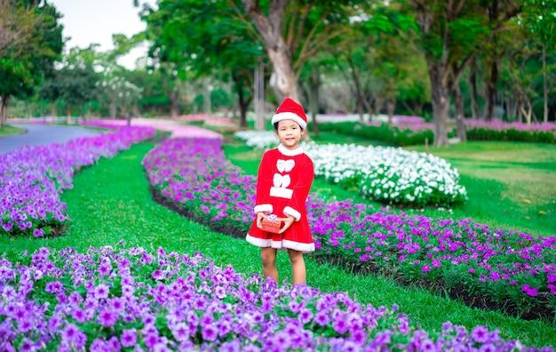 Piccola ragazza asiatica in costume rosso di babbo natale con scatola presente in giardino