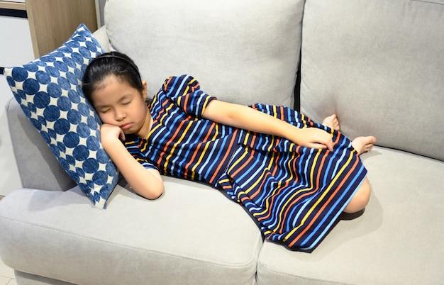 La piccola ragazza asiatica dorme su uno strato