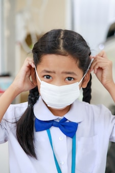Piccola ragazza asiatica in uniforme tailandese dello studente che indossa la maschera protettiva di influenza del virus, concetto di sanità, profondità di campo bassa del fuoco selezionato