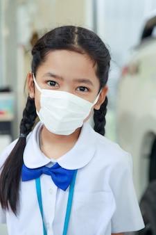 Piccola ragazza asiatica in uniforme tailandese dello studente che porta la maschera protettiva di influenza del virus