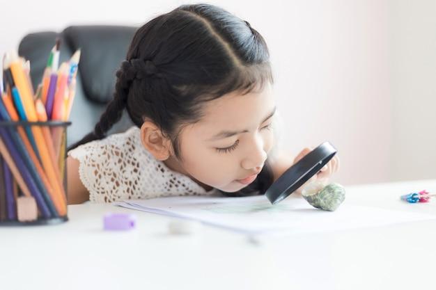 Piccola ragazza asiatica utilizzando la lente di ingrandimento facendo i compiti per il concetto di educazione selezionare messa a fuoco profondità di campo