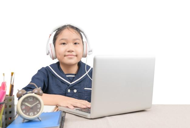 La piccola ragazza asiatica indossa le cuffie e fa i compiti con il computer portatile in linea isolato