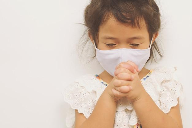 Piccola ragazza asiatica che indossa una maschera e che prega. mani giunte nel concetto di preghiera, copia dello spazio.