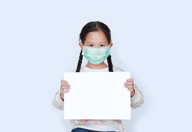 Piccola ragazza asiatica che indossa la maschera protettiva con carta bianca in bianco che mostra su fondo bianco.