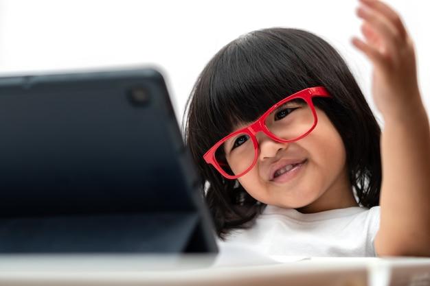 Bambina asiatica in età prescolare che indossa occhiali rossi e utilizza tablet pc su sfondo bianco, ragazza asiatica che parla e impara con una videochiamata con un tablet, concetto educativo per i bambini delle scuole.