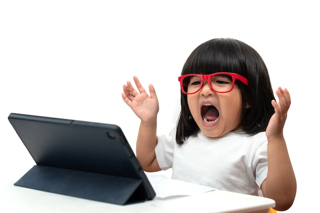 Bambina asiatica in età prescolare che indossa occhiali rossi e utilizza un tablet pc su sfondo bianco