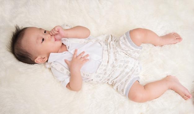 Piccolo neonato 7 mesi con il dito pollice in bocca