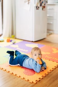Il piccolo bambino vestito di blu con una carota in mano giace sulla pancia su un tappeto colorato