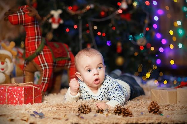 Piccolo neonato sdraiato a pancia in giù in camera con decorazioni natalizie