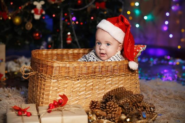 Piccolo neonato in cappello della santa che si siede in un cestino di vimini. anno nuovo e concetto di natale