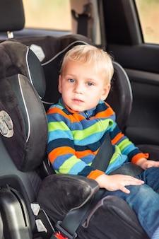 Piccolo neonato seduto su un seggiolino per auto allacciato in macchina.