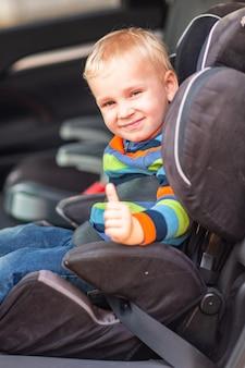 Piccolo neonato seduto su un seggiolino per auto