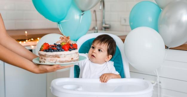 Piccolo neonato seduto nel seggiolone in cucina bianca e degustazione di torta del primo anno con frutta dalle mani della madre su sfondo con palloncini.