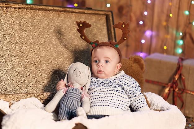 Piccolo neonato seduto in una valigia con un coniglietto giocattolo in camera con decorazioni natalizie