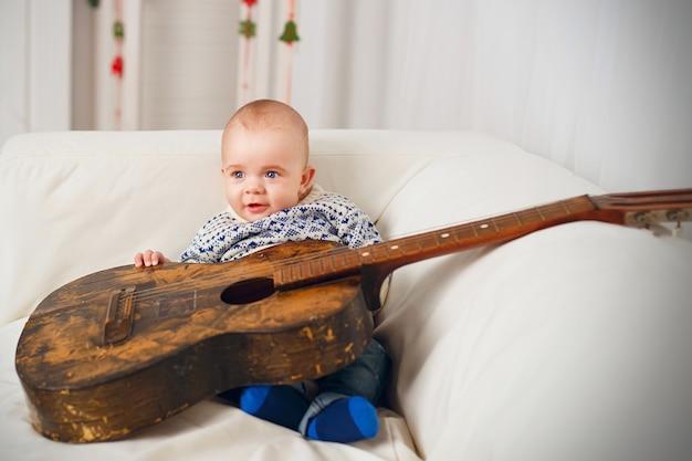 Piccolo neonato con una vecchia chitarra vintage