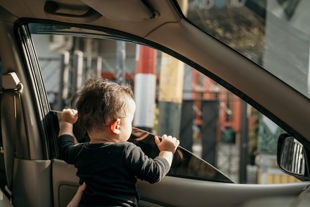Piccolo bambino in macchina quando i finestrini sono aperti durante il viaggio in auto