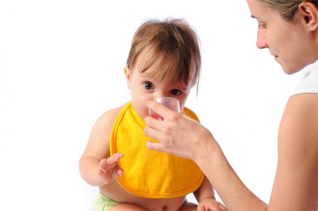 Il piccolo bambino beve l'acqua dalla tazza