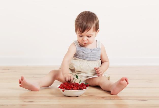 Piccolo bambino che mangia la bacca