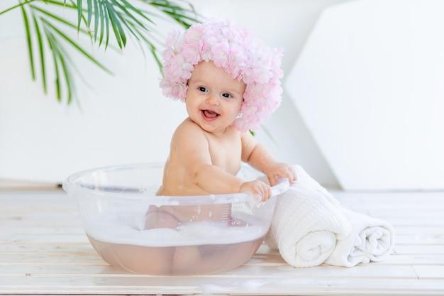 Piccola neonata in una bacinella con schiuma e acqua