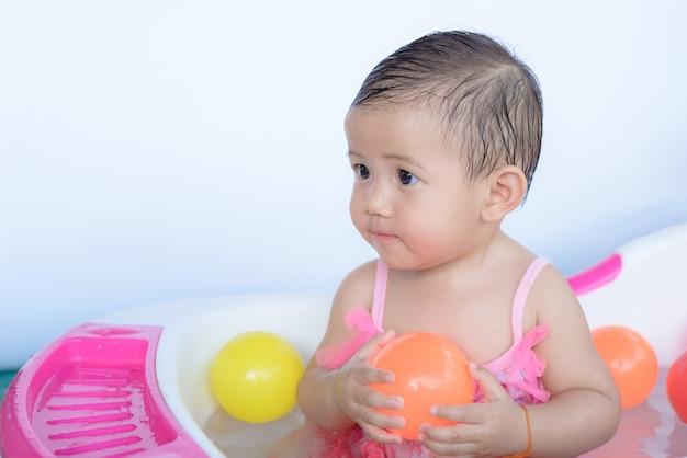 Piccola bambina nel bagno giocando a palla.