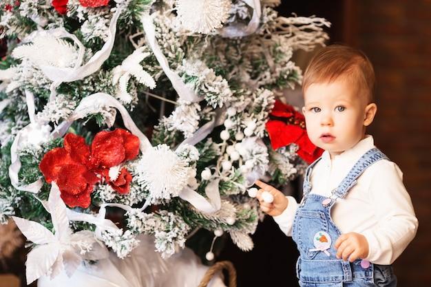 La piccola neonata decora l'albero di natale