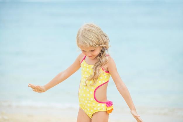 La piccola neonata è bella e felice in un costume da bagno luminoso nel pomeriggio su una spiaggia soleggiata