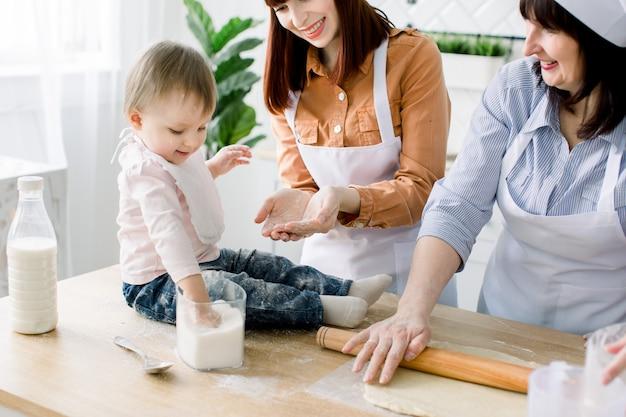 La piccola neonata sta sedendosi sul tavolo di legno alla cucina e si diverte con lo zucchero. la nonna e le sue figlie stanno cuocendo i biscotti. donne felici in grembiuli bianchi che cuociono insieme. festa della mamma