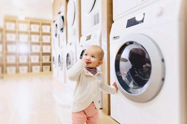 Piccola neonata che esamina una lavatrice