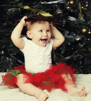 Piccola neonata vicino alla decorazione dell'albero di natale.