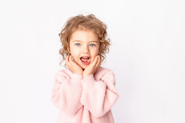 La piccola bambina in abiti invernali rosa su sfondo bianco esulta, spazio per il testo