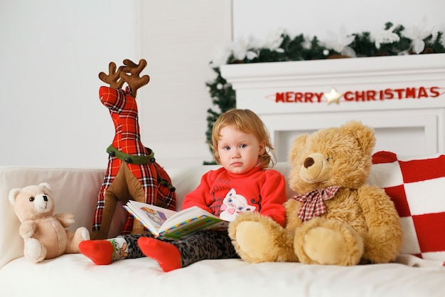 Piccola neonata che legge un libro nei suoi giocattoli decorazioni natalizie