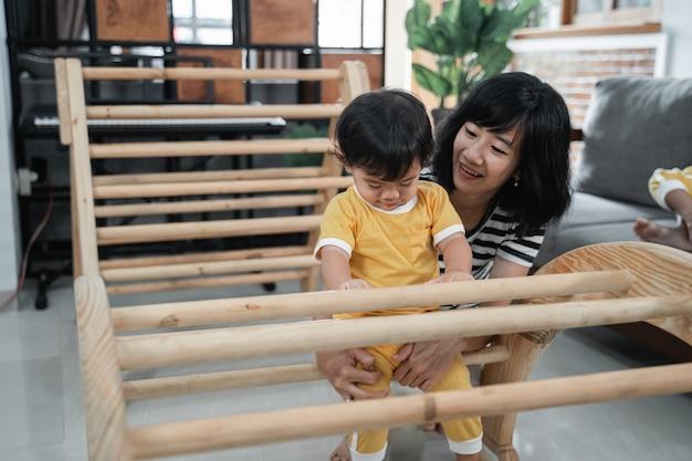 La piccola neonata si siede sui giocattoli di arrampicata pikler con sua madre mentre gioca insieme in casa