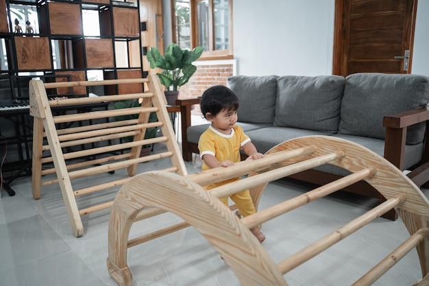 Piccola neonata che si siede sui giocattoli rampicanti del pikler nella casa