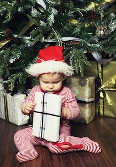 Piccola neonata con la confezione regalo vicino all'albero di natale.