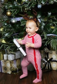 Piccola neonata con la confezione regalo vicino a decorare l'albero di natale. tempo felice.