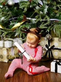 Piccola neonata con il contenitore di regalo vicino all'albero di natale di decorazione. tempo felice.