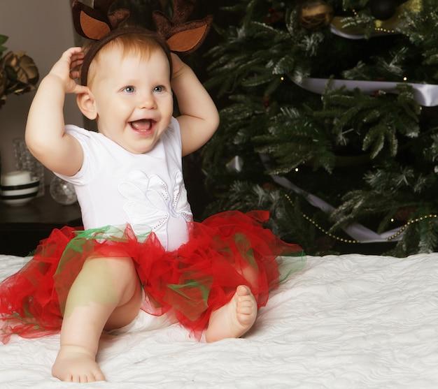 Piccola neonata con il contenitore di regalo vicino all'albero di natale di decorazione.