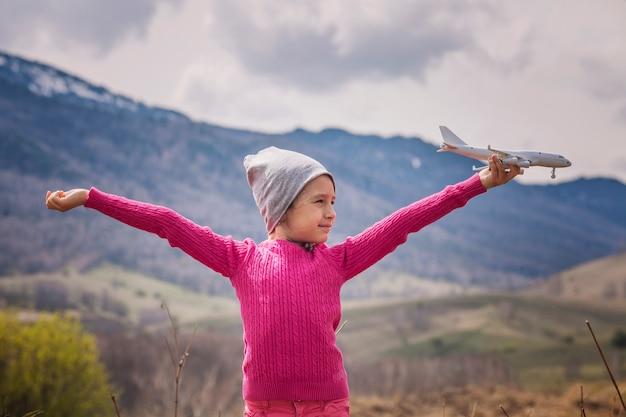 Piccola neonata con l'aeroplano bianco del giocattolo nelle mani su uno sfondo di montagne e cielo